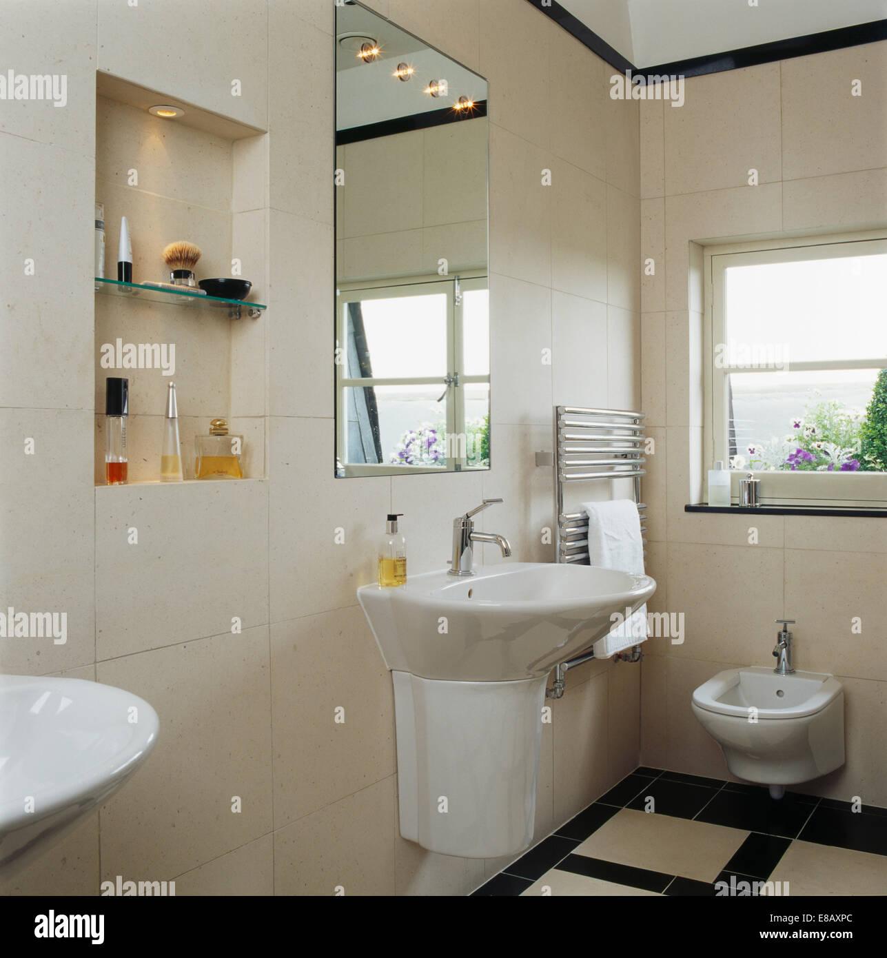 Mirror above wall mounted basin in modern tiled bathroom for Bathroom alcove shelves