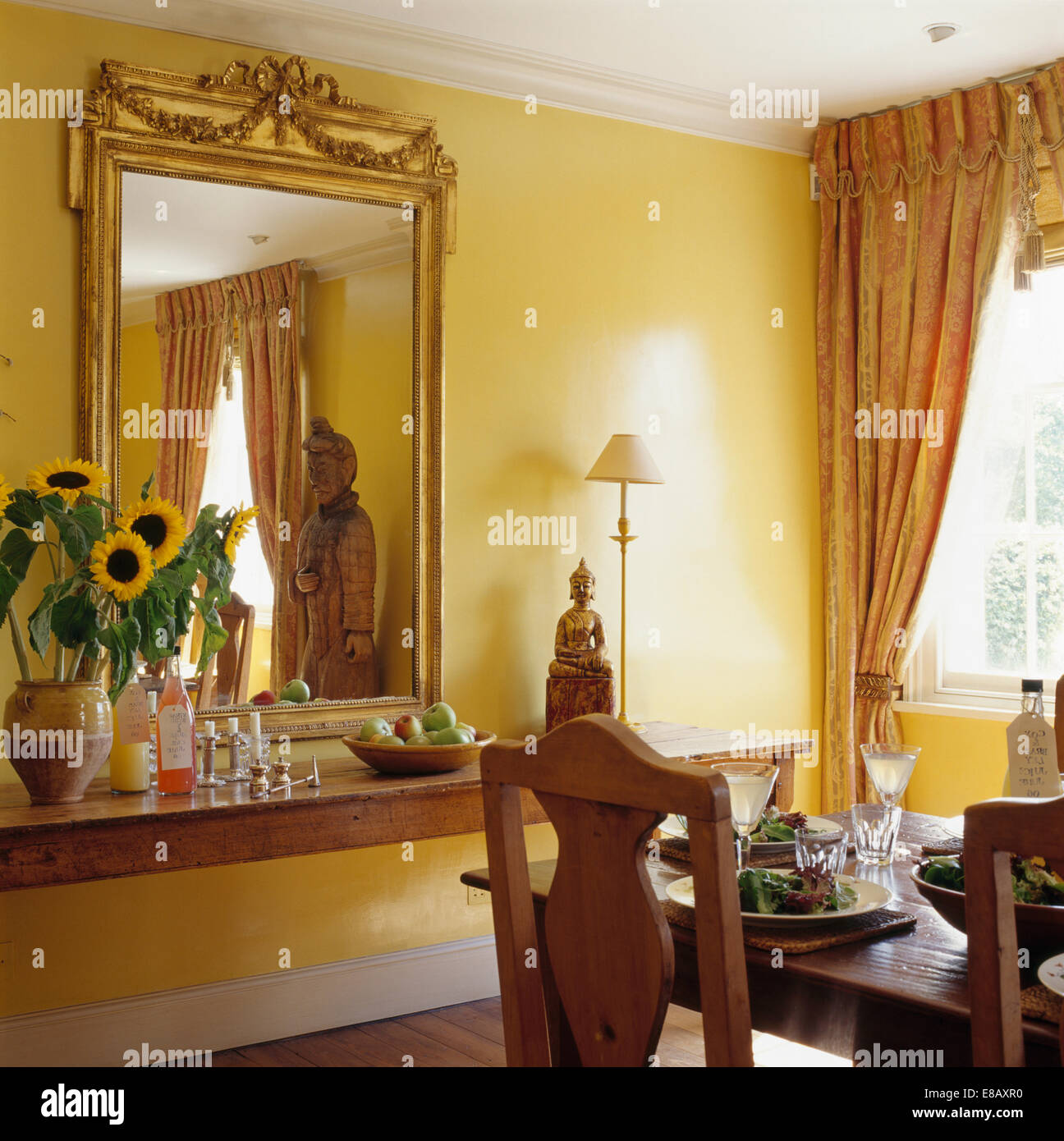Large gilt-framed antique mirror above old pine table with vase of ...
