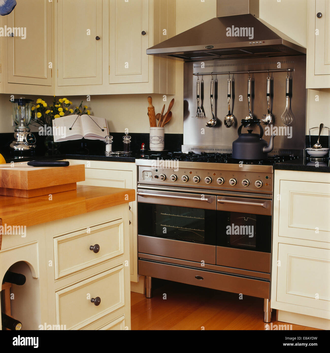 Stainless-steel range oven and splash-back in country kitchen with cream  painted units