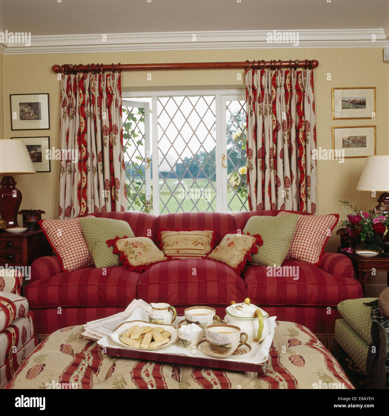 Stock Photo   Tea Tray On Stool In Front Of Red Sofa And Lattice Window  With Patterned Curtains In Cottage Living Room Part 69