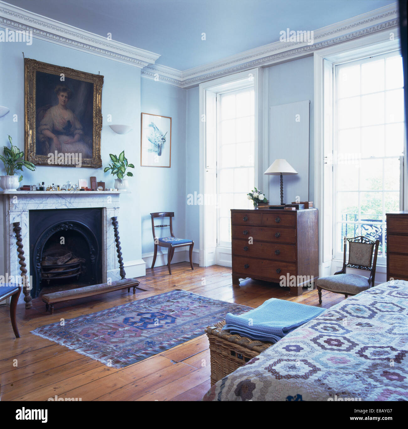 Large picture above marble fireplace in pale blue bedroom with ...