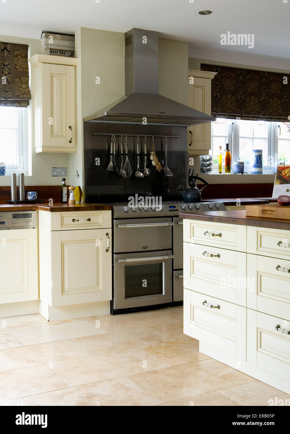 Cream travertine floor tiles in modern kitchen with large cream travertine floor tiles in modern kitchen with large stainless steel range oven and cream fitted units dailygadgetfo Gallery