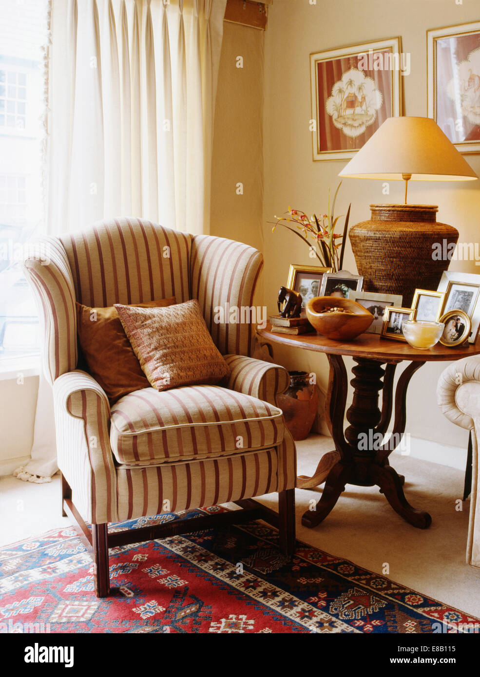 Beige Striped Wing Chair Beside Antique Circular Table With Lighted Lamp  And Group Of Framed Photographs