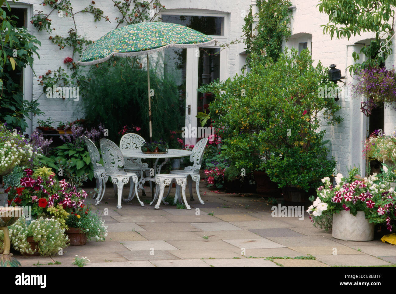 Green Umbrella Above White Wrought Iron Table And Chairs On Patio With Pots  Of Colorful Annuals