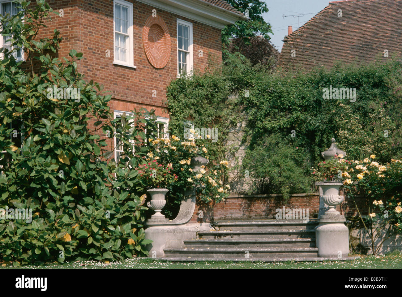 Stock Photo   Urns On Plinths Beside Stone Steps To House In Large Country  Garden With Cream Roses