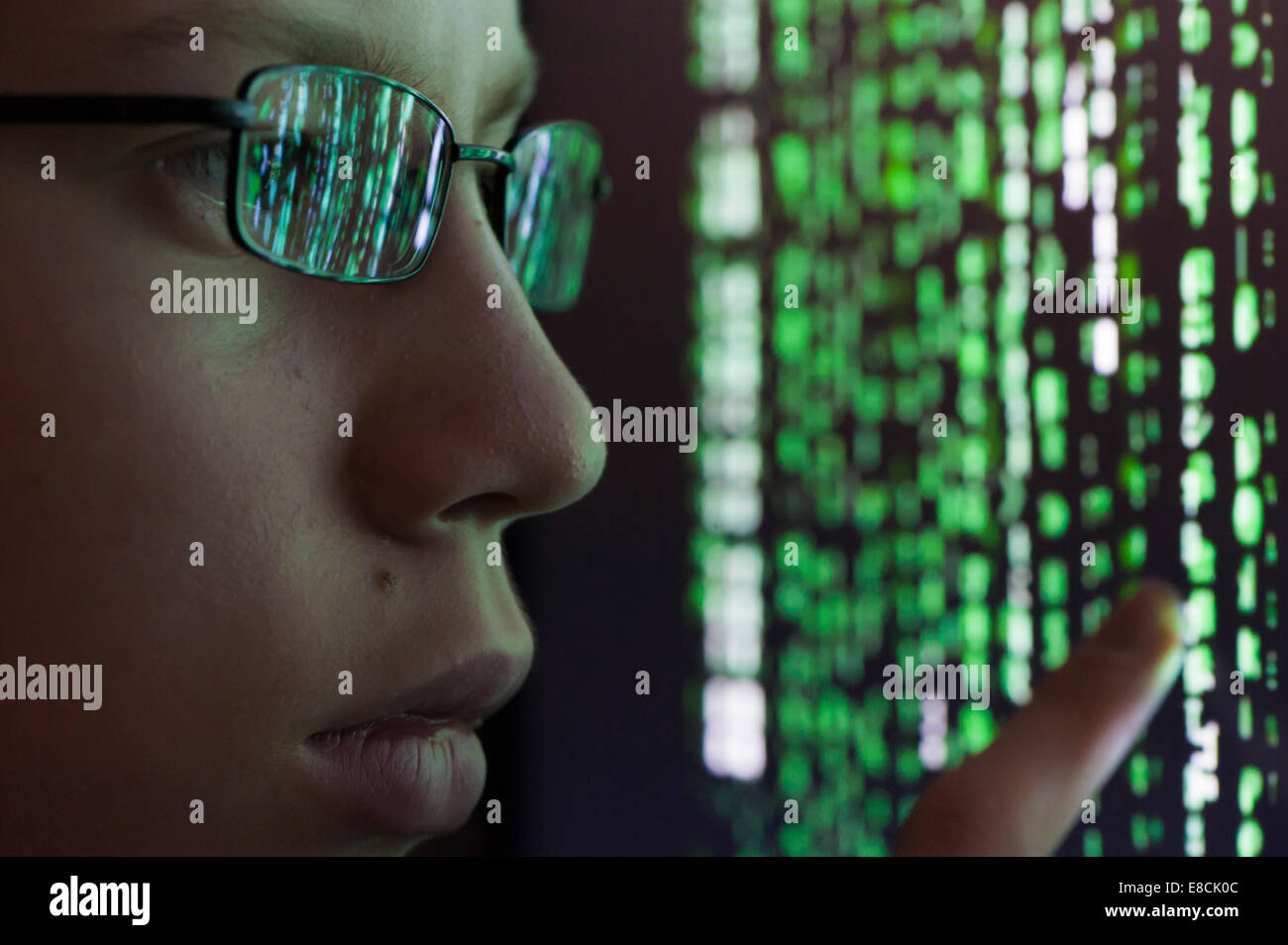 A young man with glasses is watching futuristic symbols on a a young man with glasses is watching futuristic symbols on a computer screen symbols are reflecting in the mans glasses biocorpaavc Choice Image