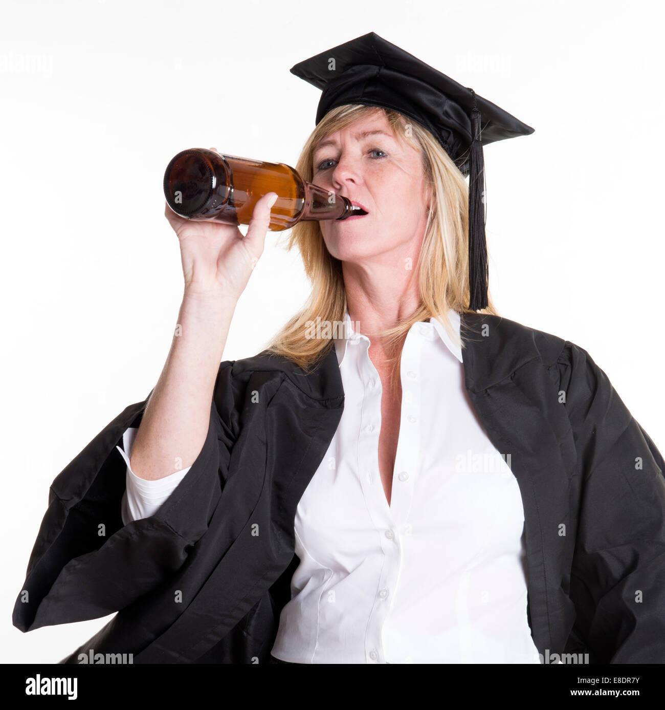 Beer drinking University student wearing cap and gown drinking ...