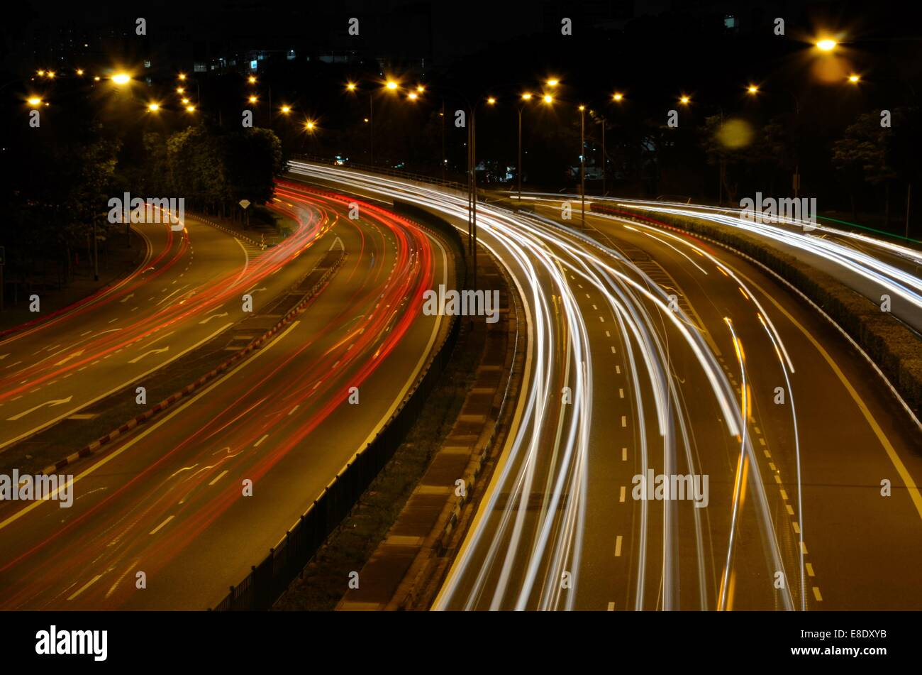 Red and white traffic car light beam trails on Braddell Road ... for Traffic Light On Road At Night  587fsj