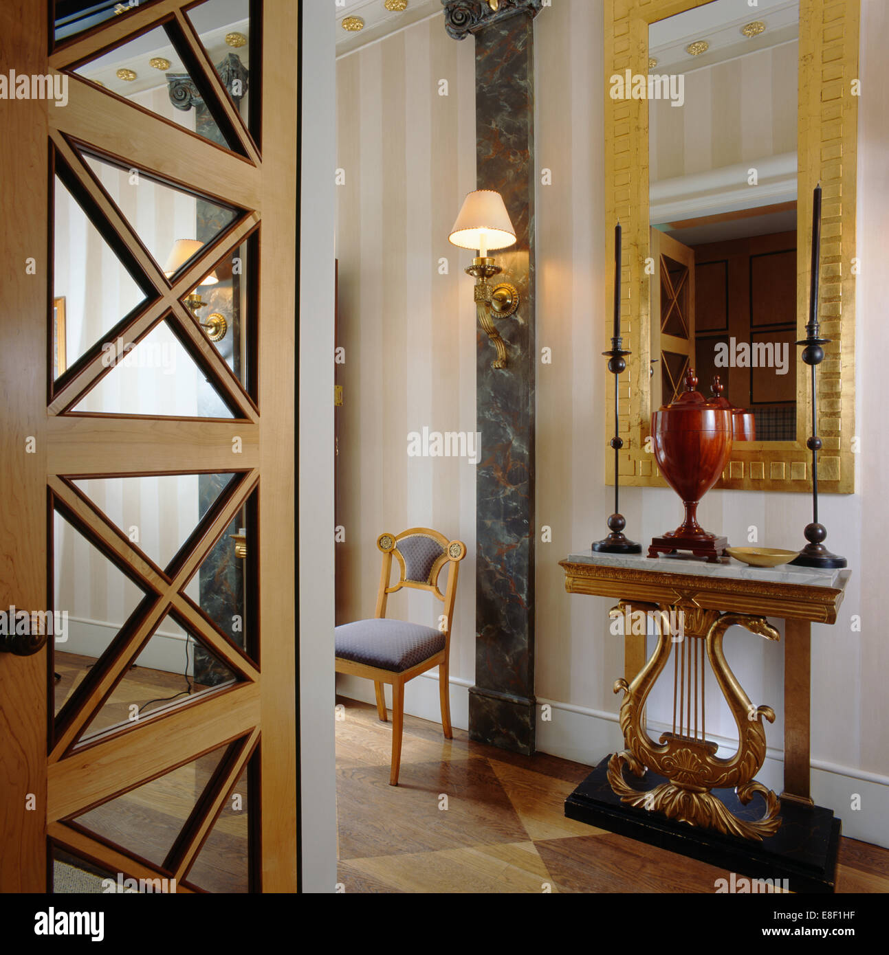 Mirror Above Ornate Console Table With Tall Candles In Elegant Hall With  Striped Wallpaper And Angular