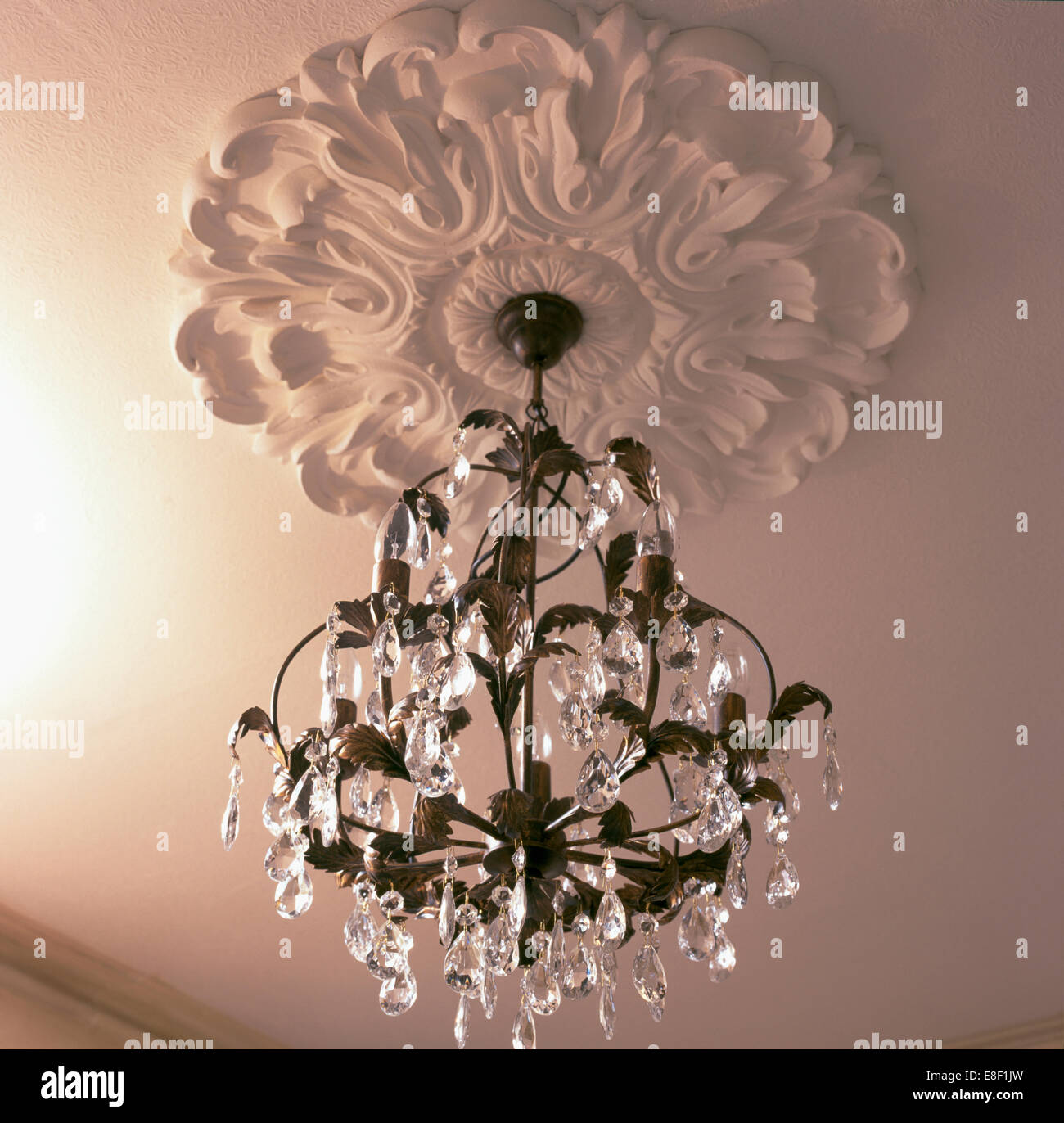 Close up of glass chandelier hanging from ornate plaster ceiling close up of glass chandelier hanging from ornate plaster ceiling rose arubaitofo Images