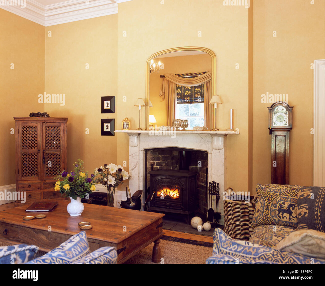 Gilt mirror above marble fireplace with wood-burning stove in ...