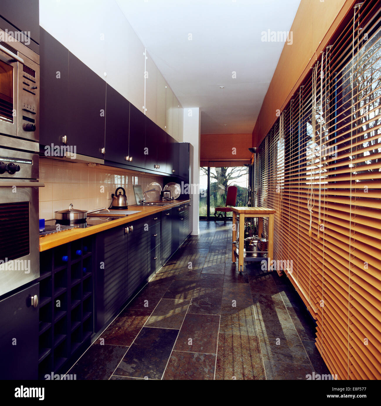 Modern Galley Kitchen Wooden Flooring In Modern Galley Kitchen With French Doors Open To