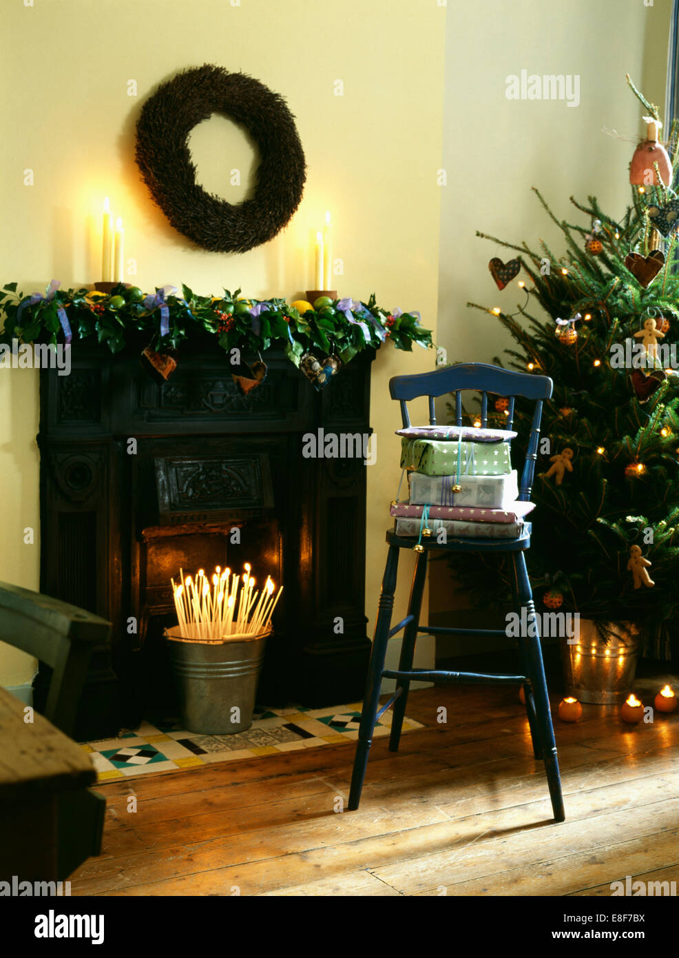 wreath above fireplace with fresh foliage garland and bucket of