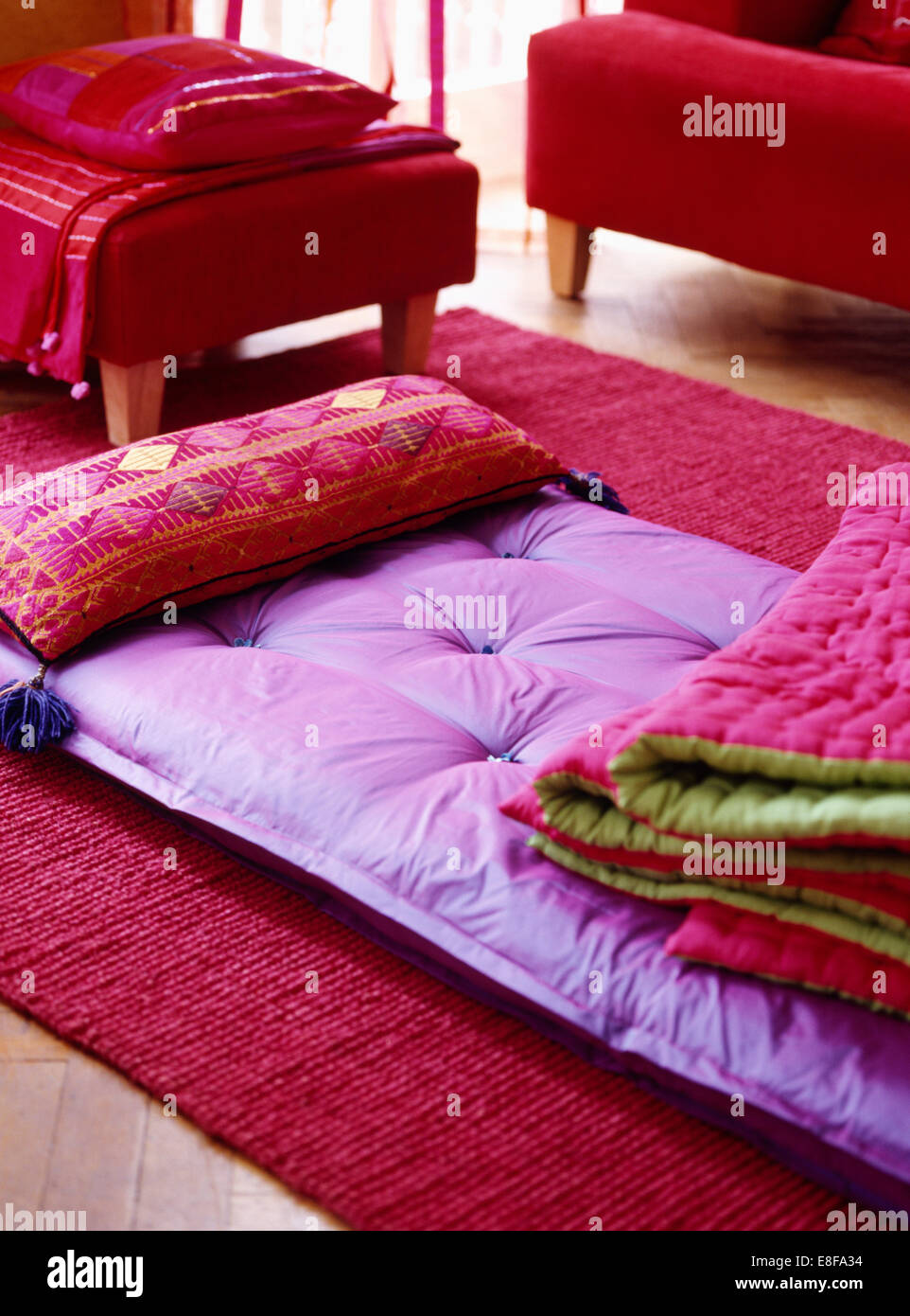 close up of folded pink green quilt on purple silk futon mattress with pink patterned cushion close up of folded pink green quilt on purple silk futon mattress      rh   alamy