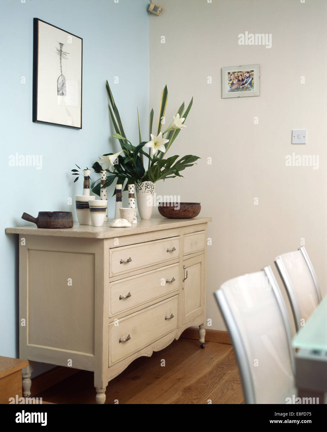 Ceramic vases and vase of white lilies on cream sideboard in ceramic vases and vase of white lilies on cream sideboard in modern dining room with single pale blue wall reviewsmspy