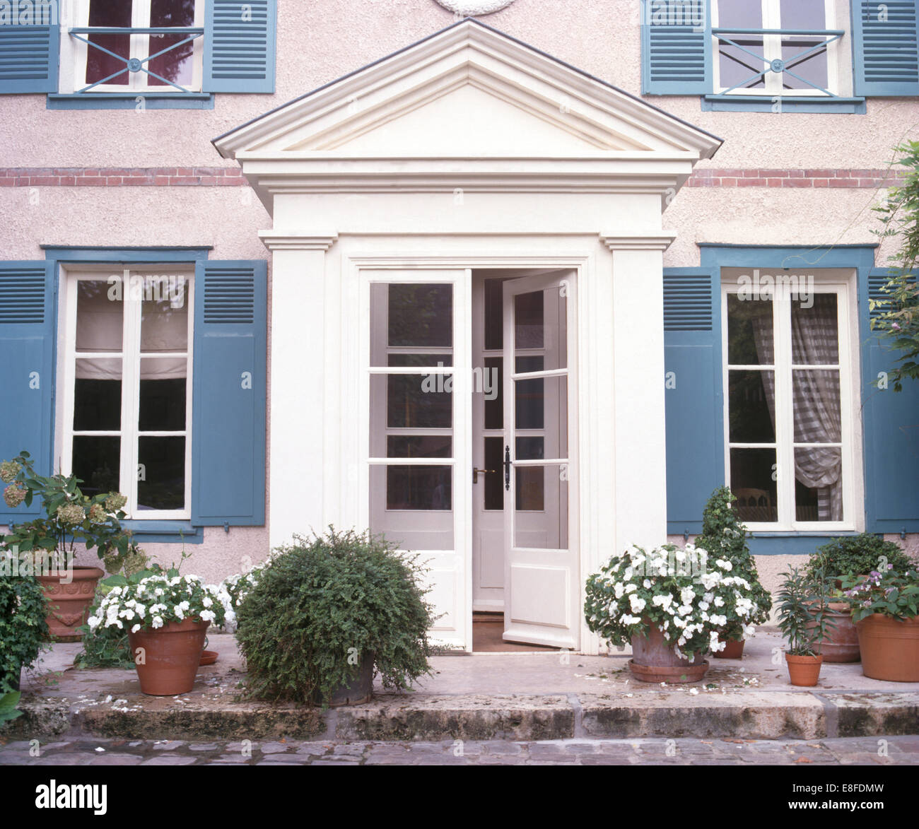 White impatiens in pots on either side of half glazed for French doors with windows either side