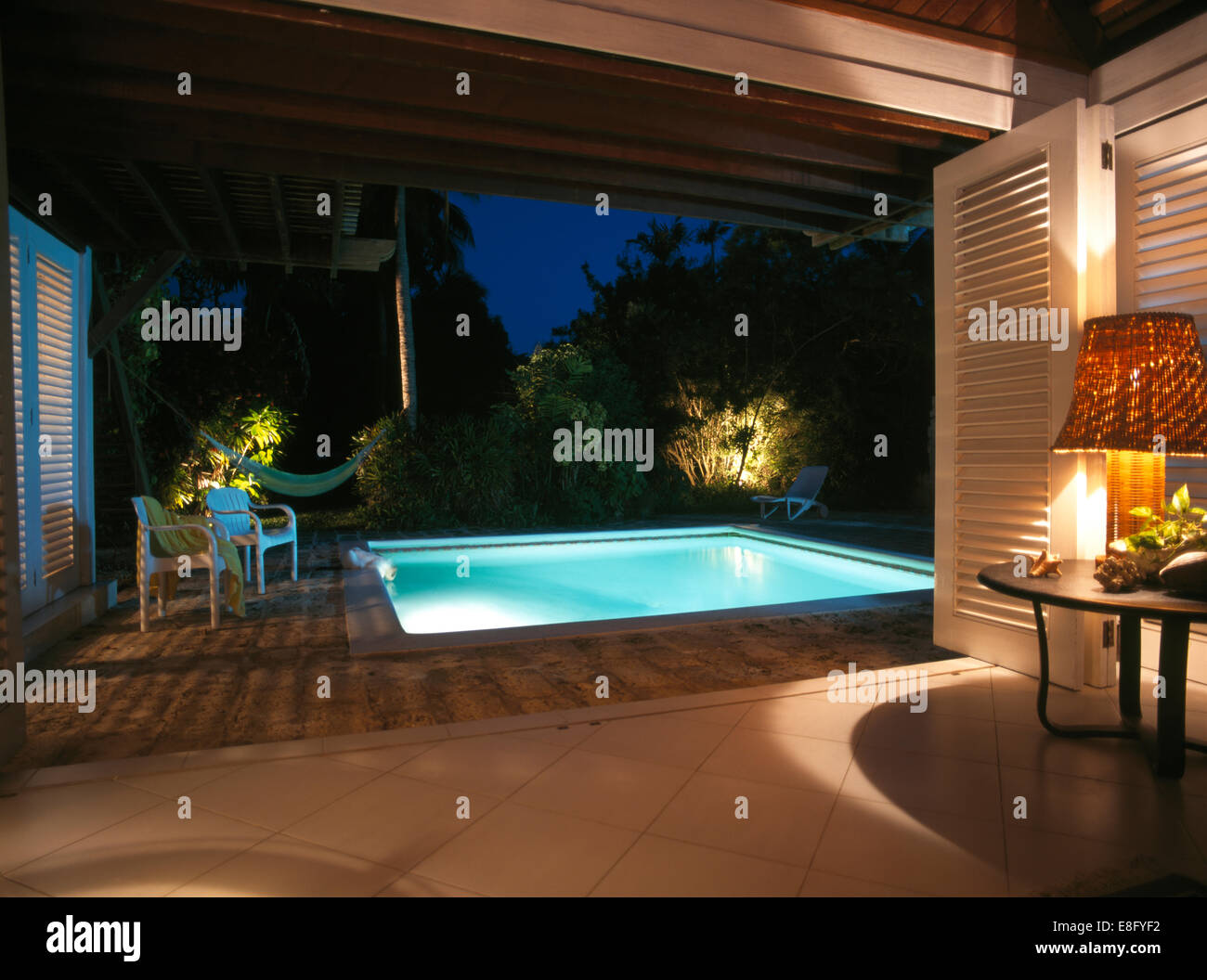 House Under Pool lighting around under-lit swimming pool in garden of modern house