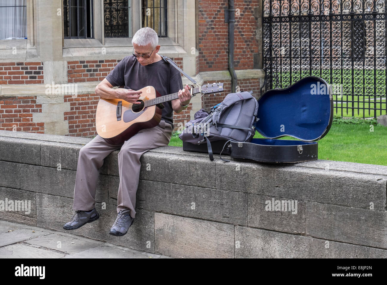 man-busking-on-guitar-sat-on-wall-st-joh