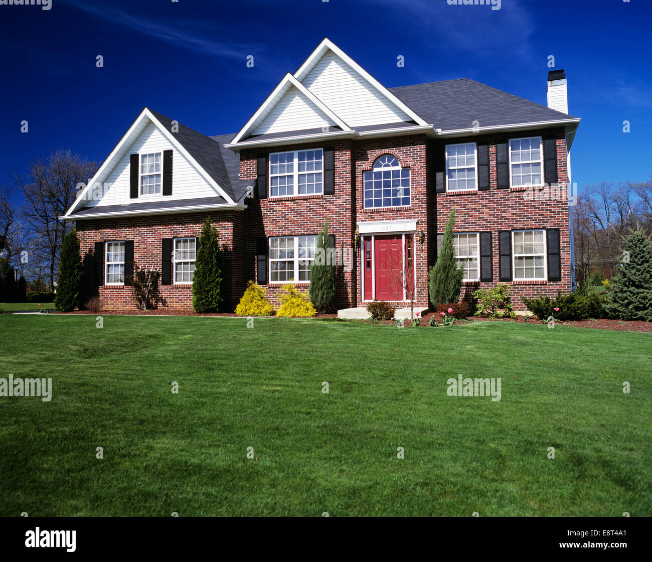 Red front door on brick house - Stock Photo Two Story Brick House With Landscaped Lawn And Red Front Door