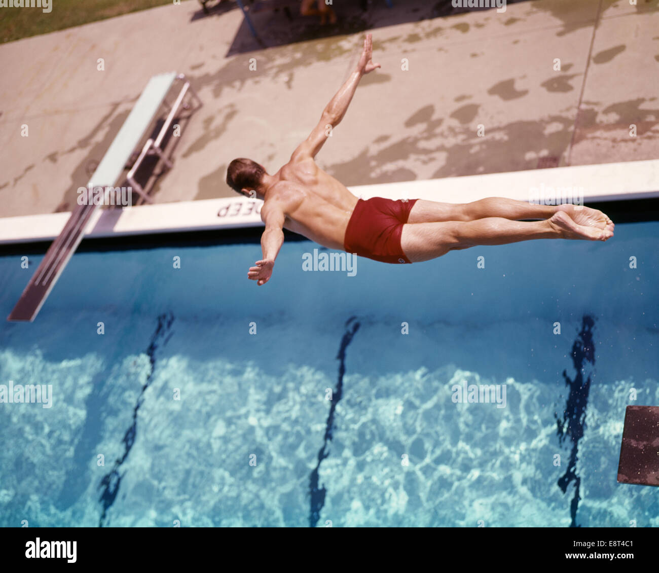 1960s MAN IN RED SWIM TRUNKS DIVING INTO SWIMMING POOL