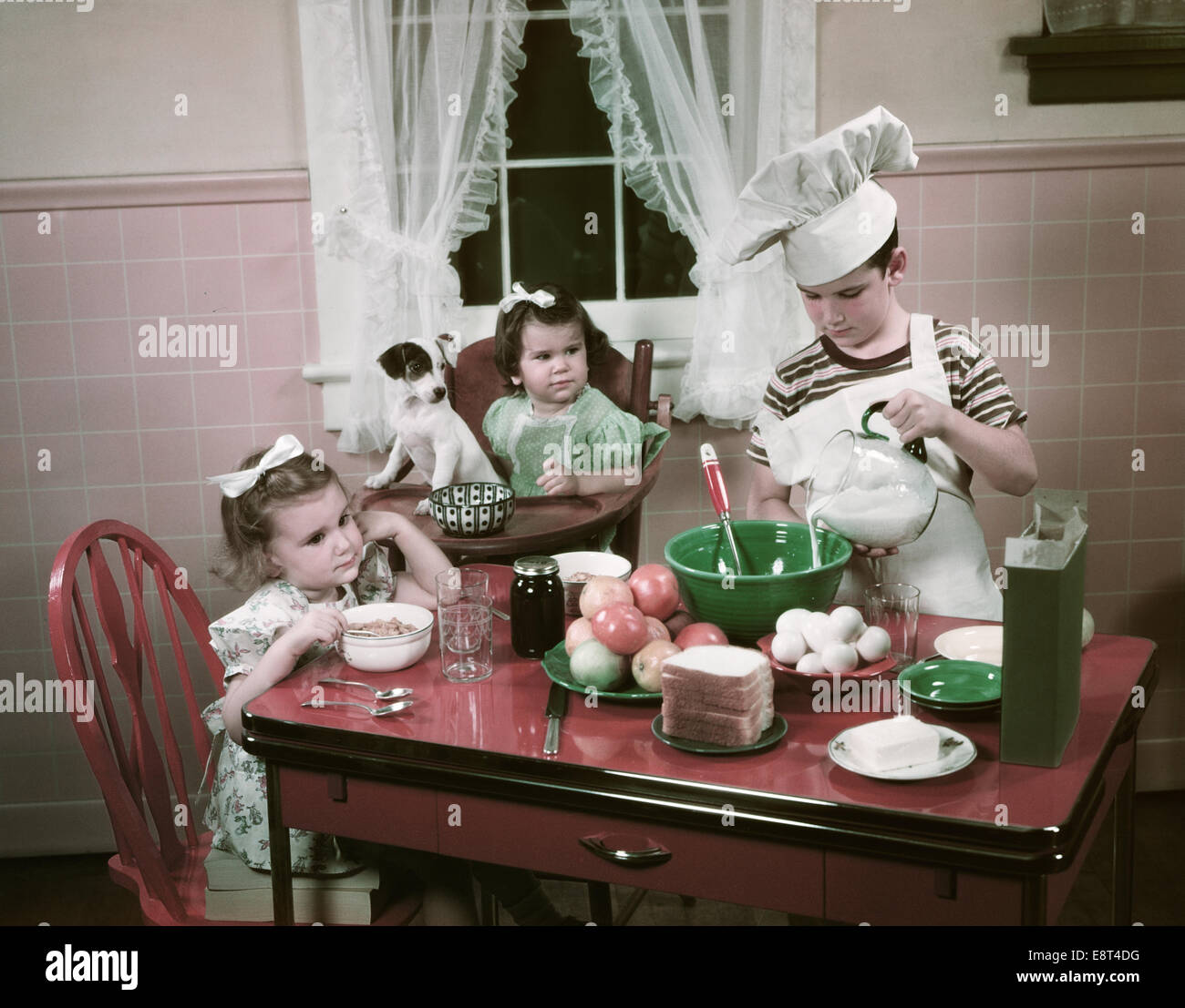 1940s 1950s children two girls at kitchen table with puppy and boy E8T4DG