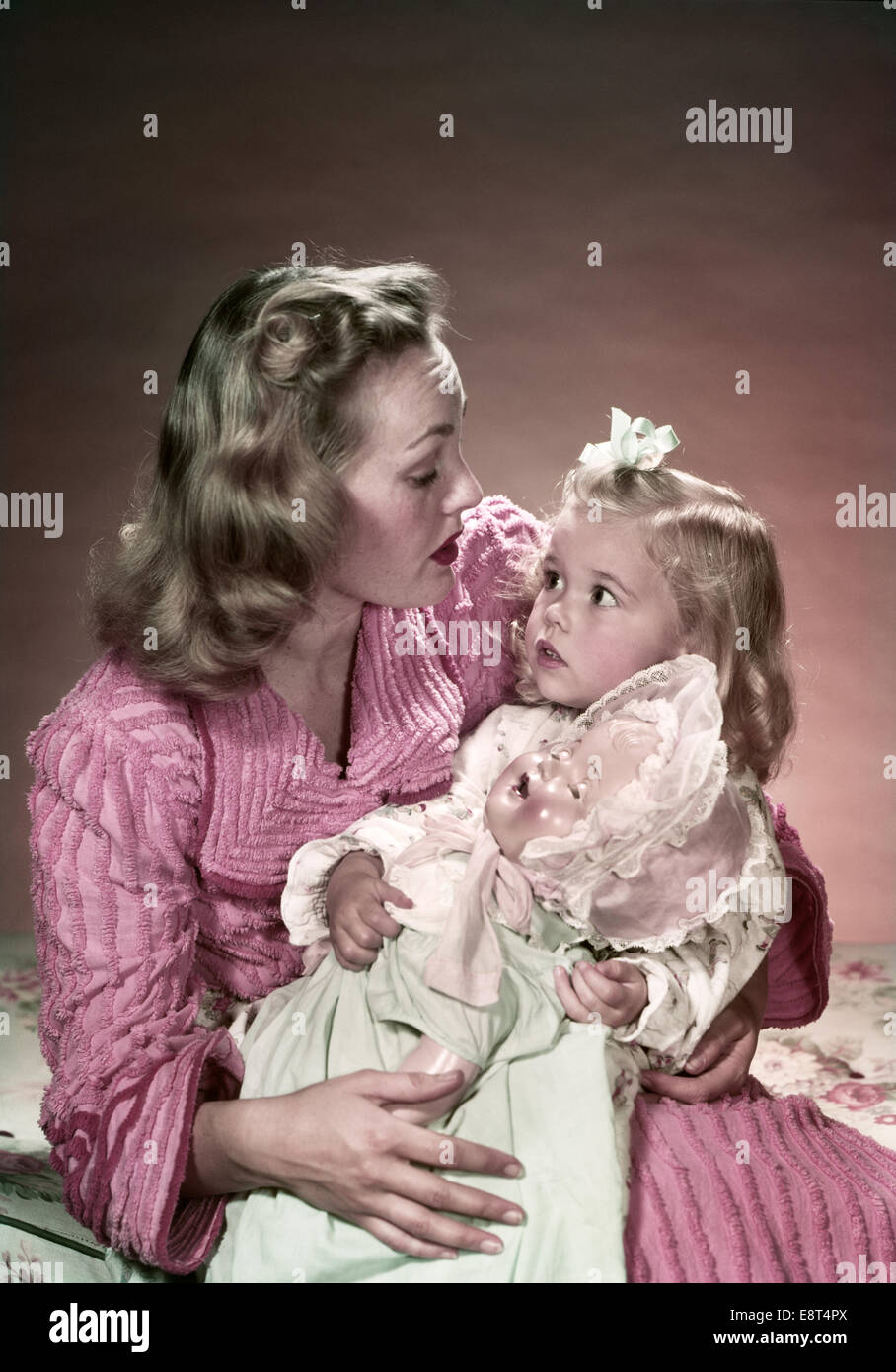 1940s Mother Sitting On Bed Holding Daughter On Lap With