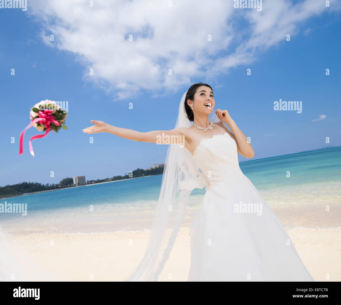 Mixed Race Asian American Bride In White Wedding Dress Throwing Bouquet At Destination Beach Okinawa Japan