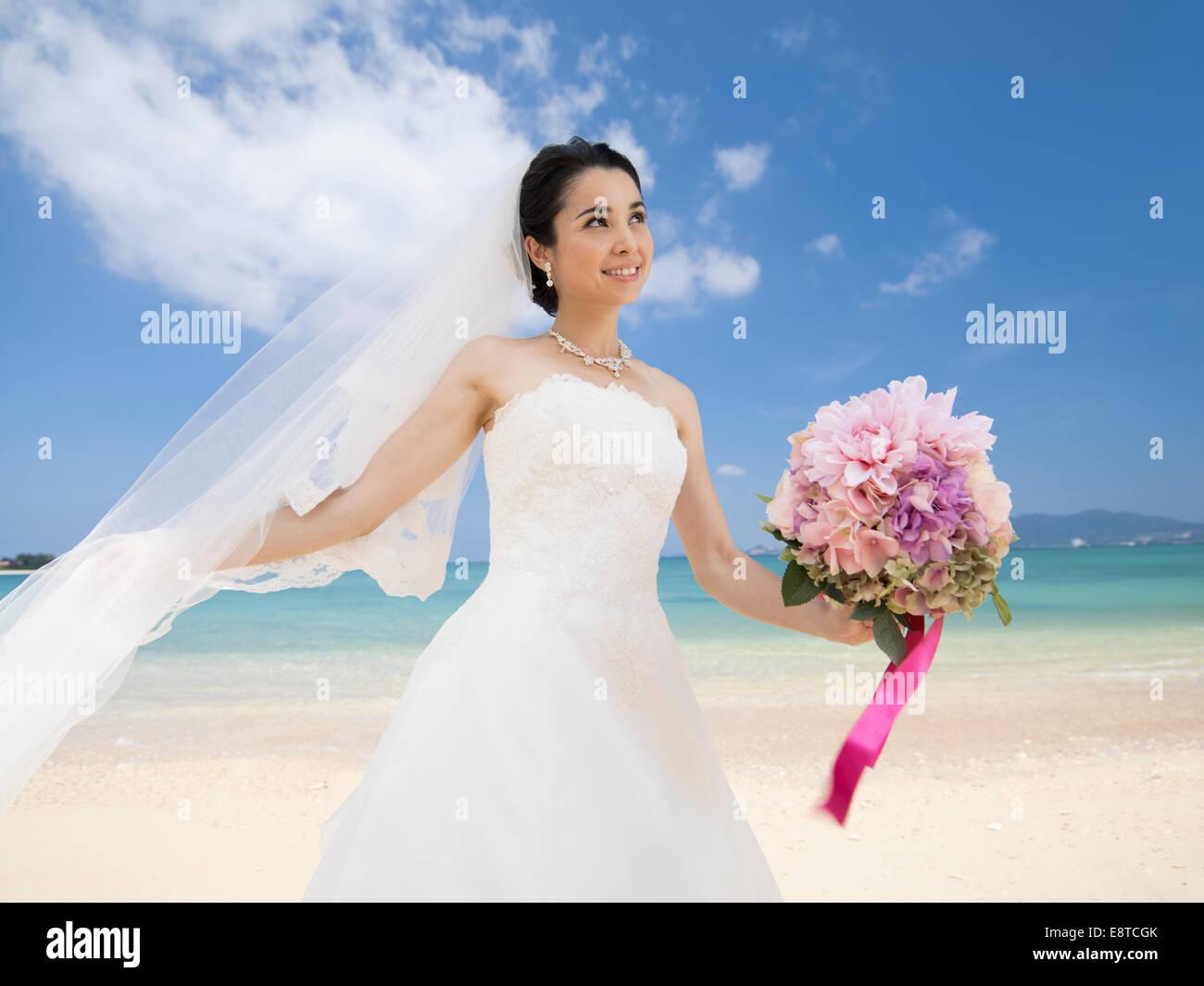 Mixed Race Asian American Bride In White Wedding Dress At Destination Beach Okinawa Japan