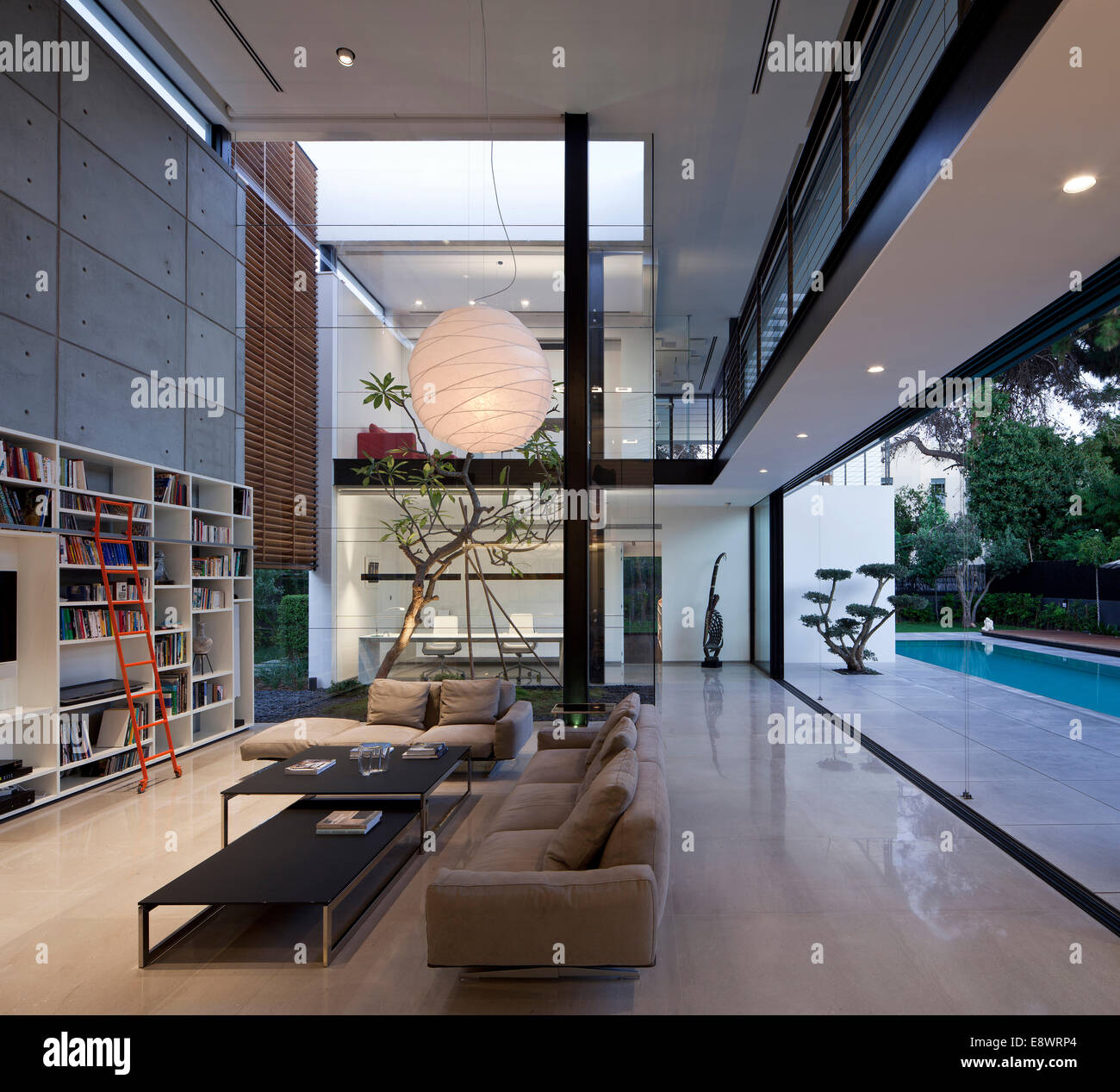 Double Height Living Room With Bookcase And Large Pendant Light In Dahan House Israel Middle East