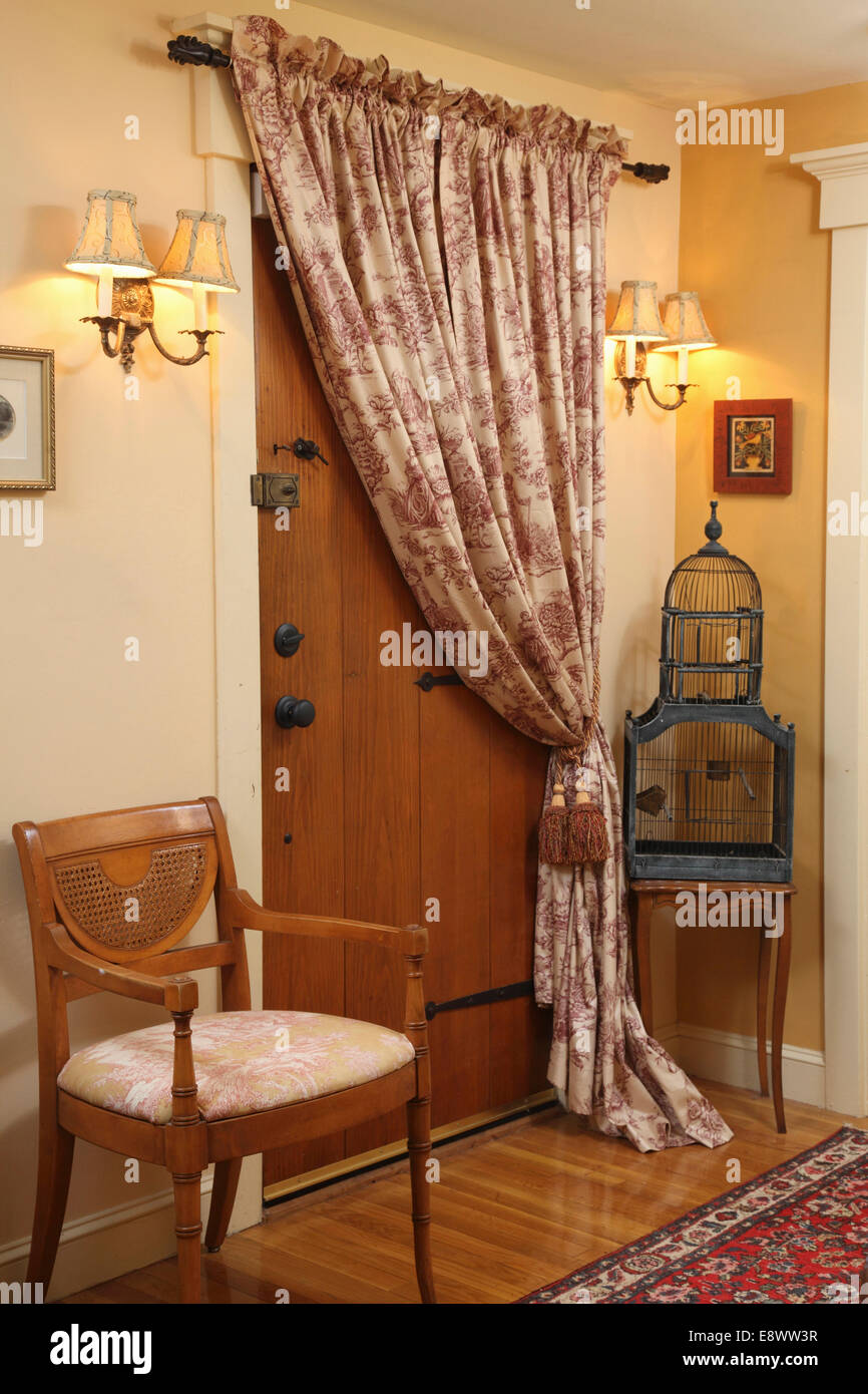 Wooden Front Door With Curtain Over It And Wall Sconces In USA Home
