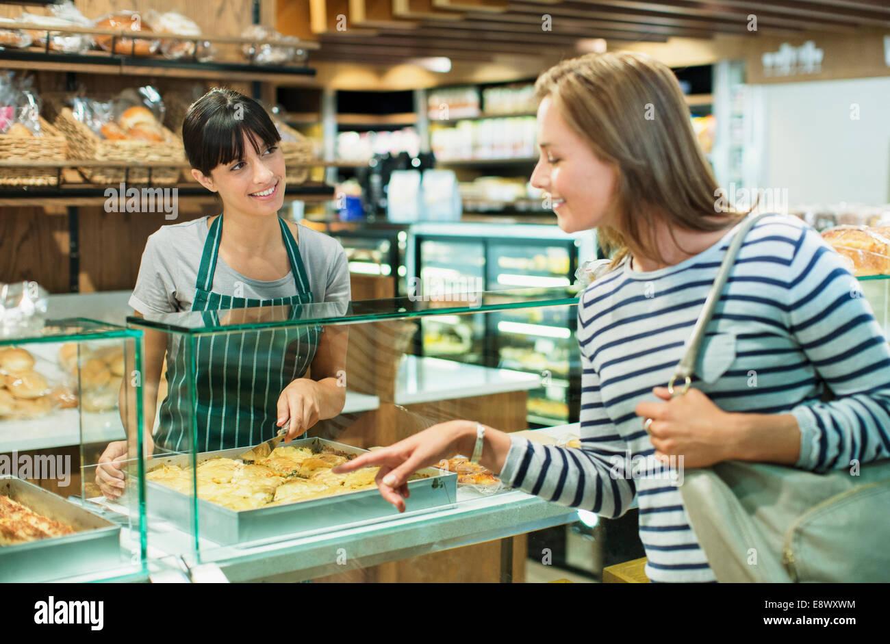 clerk serving customer at deli counter in grocery store stock clerk serving customer at deli counter in grocery store