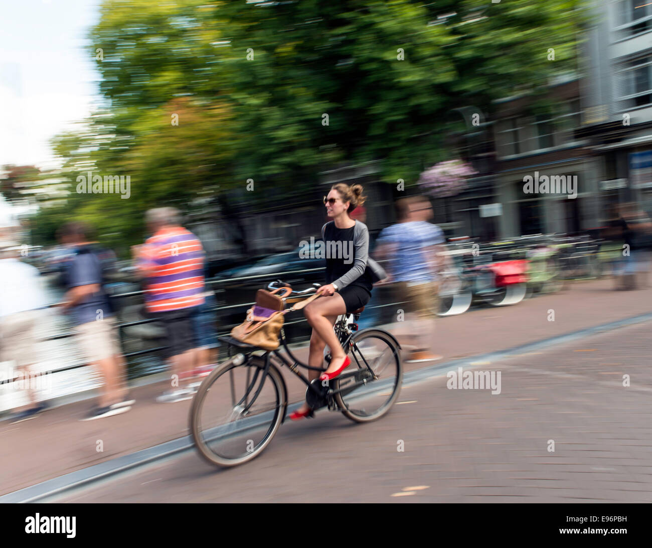 young-woman-riding-bicycle-in-amsterdam-
