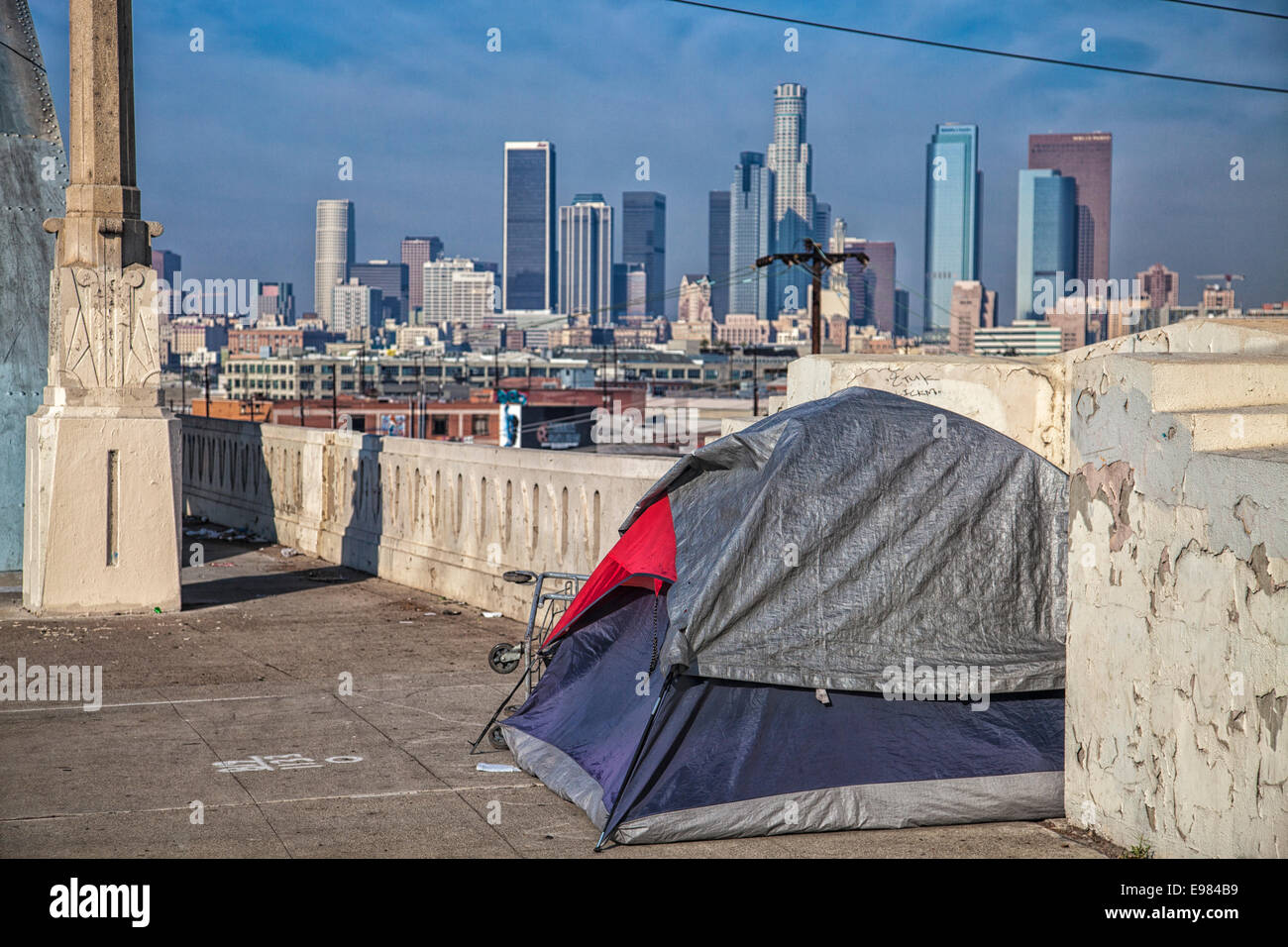 Tent of homeless person on 6th Street Bridge with Los Angeles skyline in the background. California USA & Tent of homeless person on 6th Street Bridge with Los Angeles ...