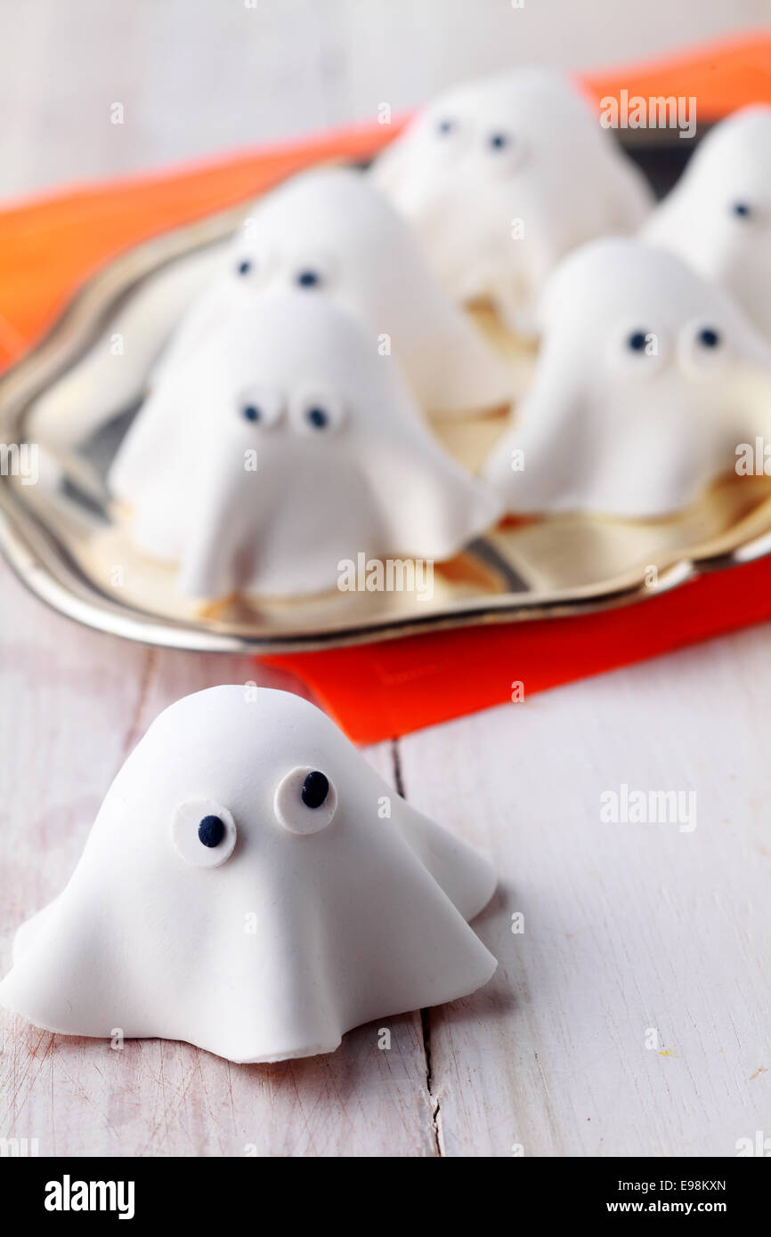 ghost halloween decorations or appetizers made with white pastry or marzipan for a party celebration or trickand treat treats