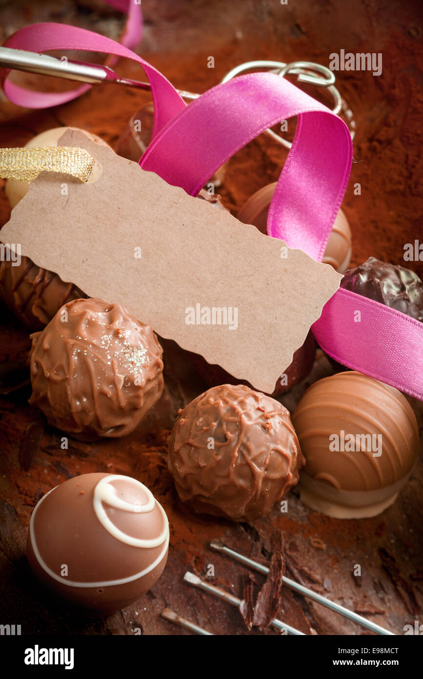 Handmade gourmet chocolates with a decorative pink ribbon and a ...