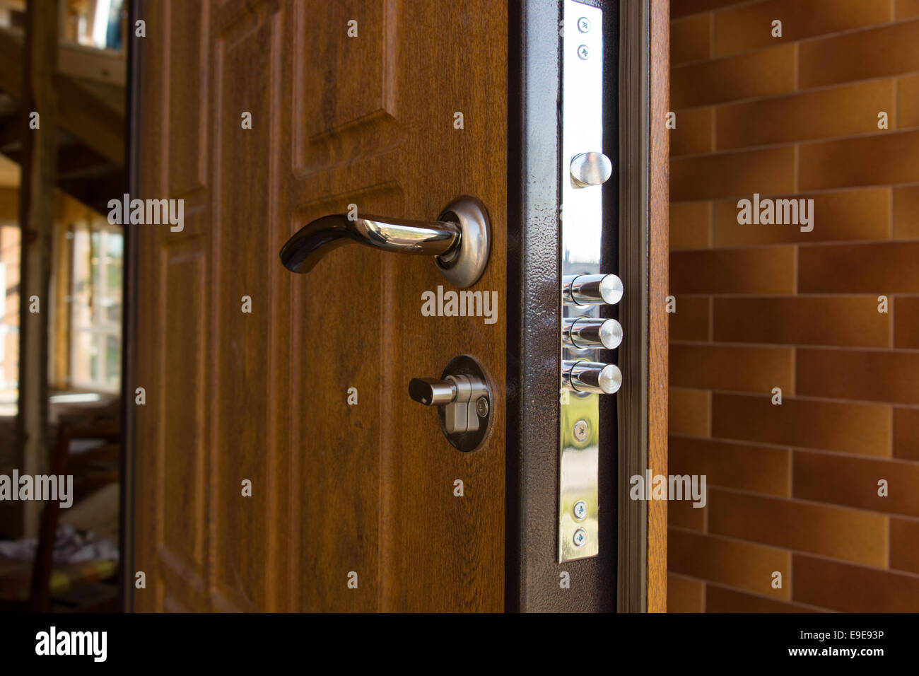 New steel three bolt door lock installed on the wooden front door of ...
