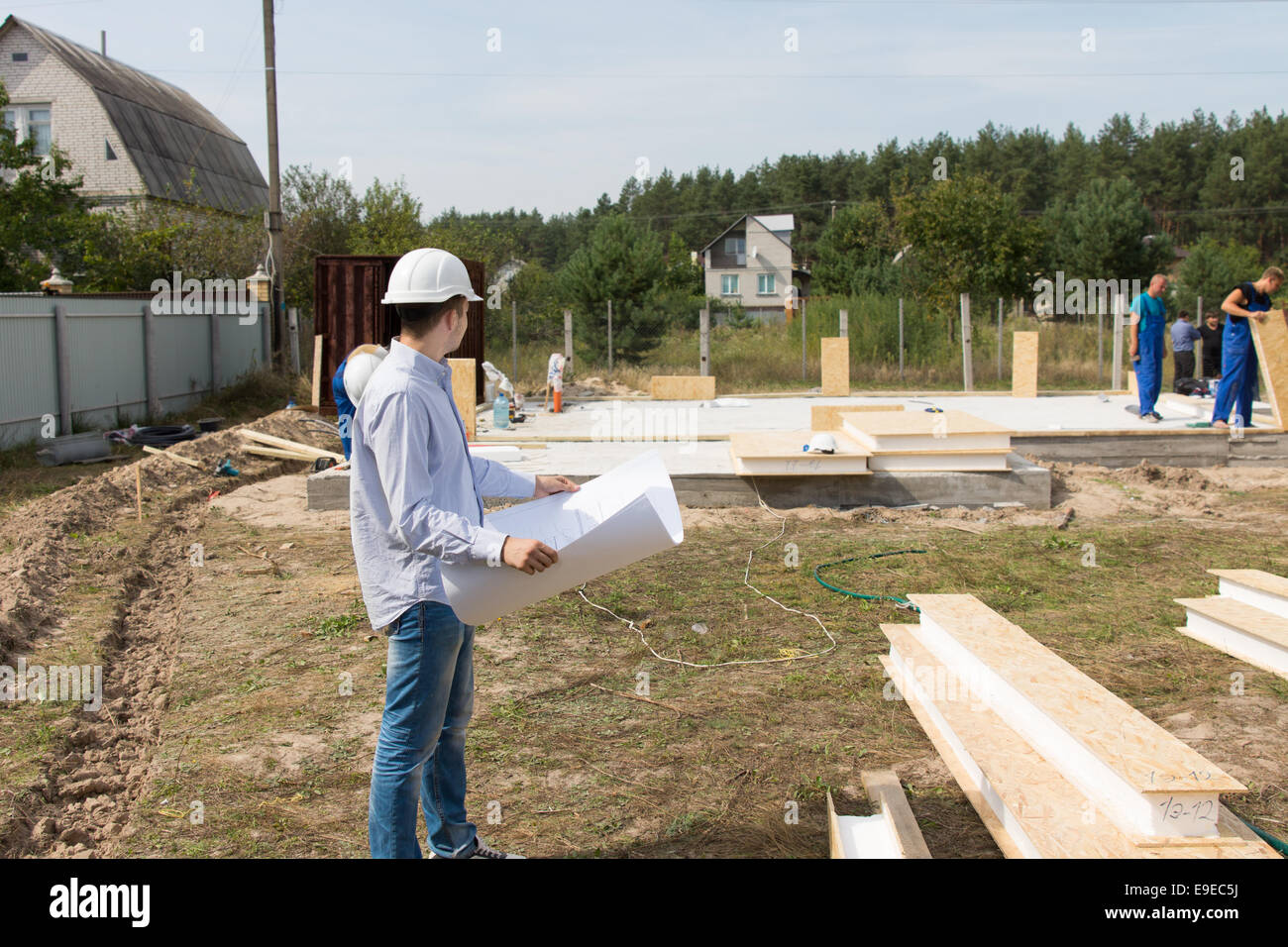 Foreman checking building supplies on site standing in front of a foreman checking building supplies on site standing in front of a stack of lumber and timber with a blueprint in his hands watching workmen working malvernweather Image collections