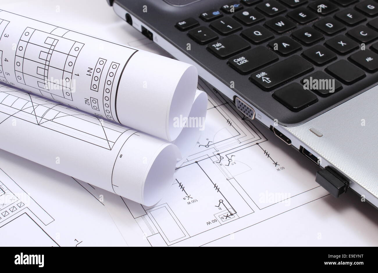 rolls of electrical diagrams with construction drawings of house and laptop drawings and accessories for the projects engineer