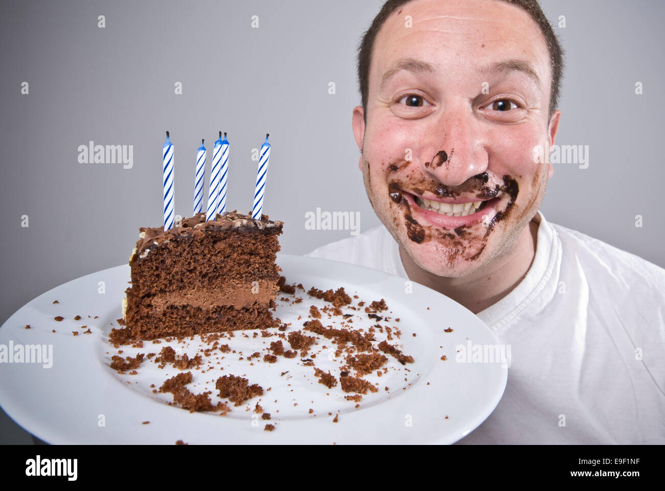 Images Of Eaten Birthday Cake : a man holds up a slice of chocolate birthday cake looking ...