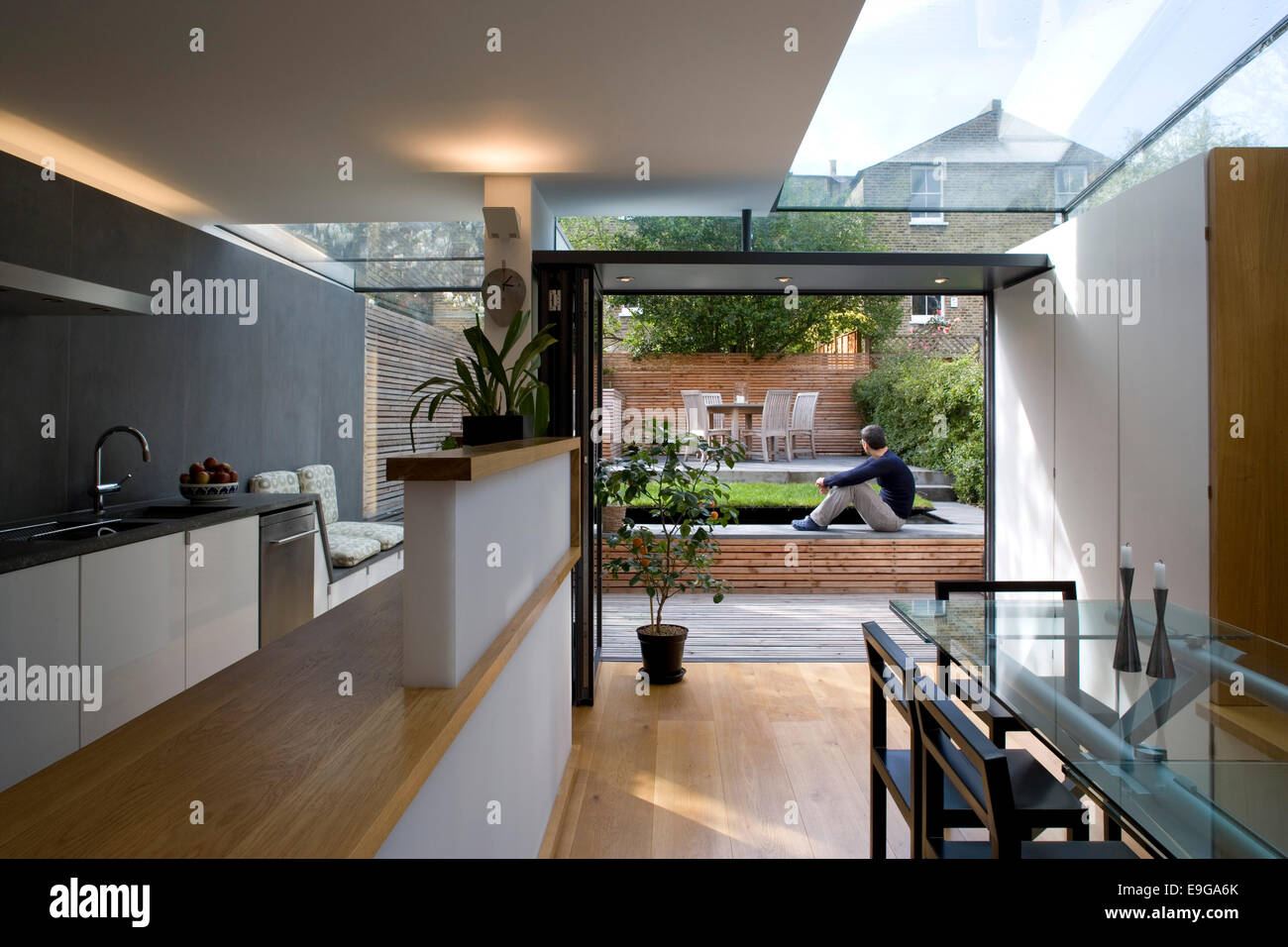 View from open plan kitchen and diner to garden in modern for Plan de barbecue exterieur
