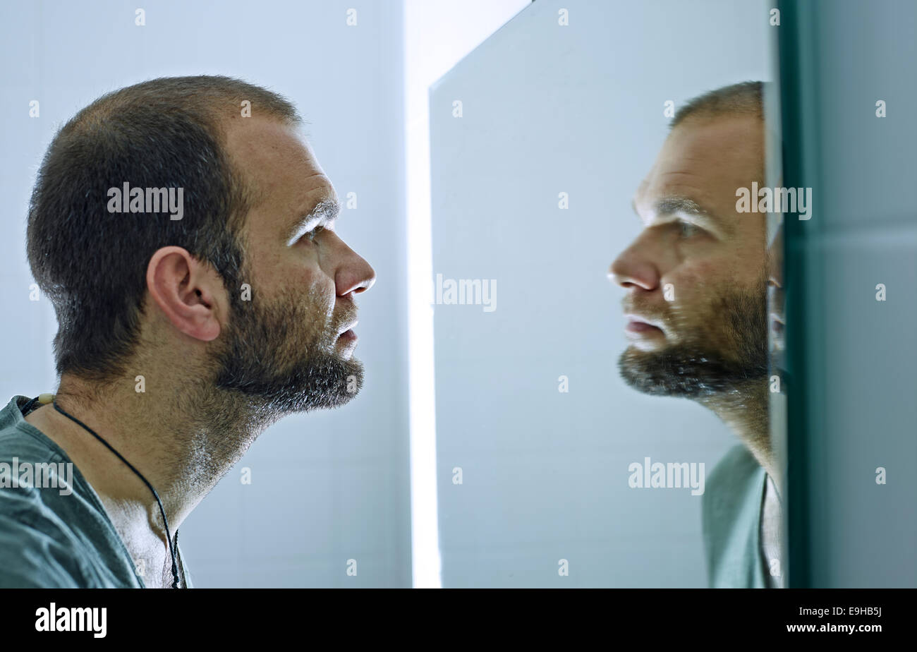looking into a mirror. man with a beard looking into mirror