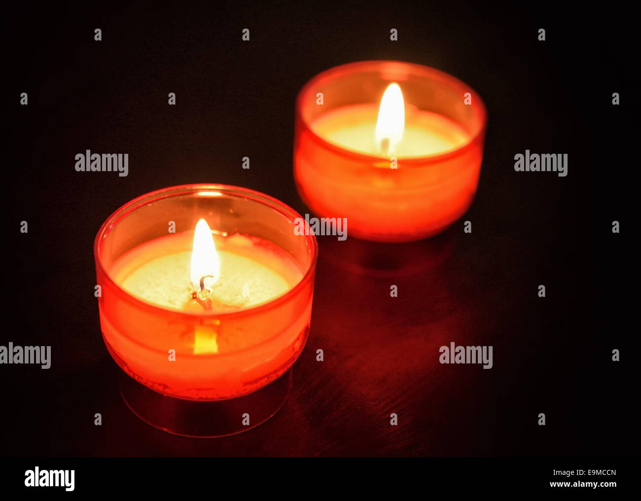 Dark room with candle light - Red Firing Candles On Wooden Table In Dark Room Closeup Image