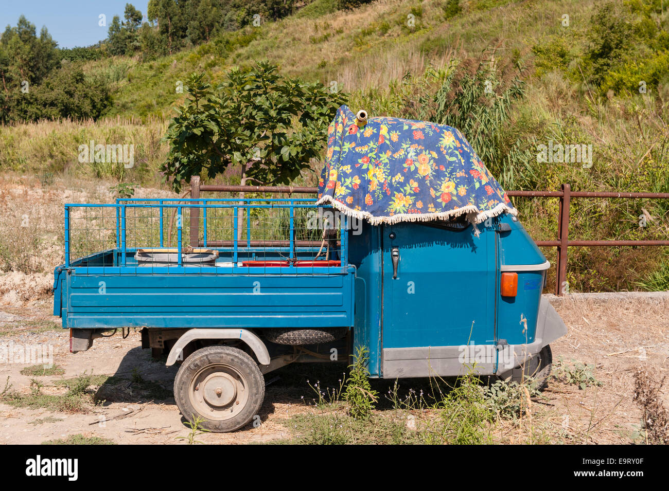 a piaggio ape 50 three wheeler shaded from the summer sun in a stock photo royalty free image. Black Bedroom Furniture Sets. Home Design Ideas
