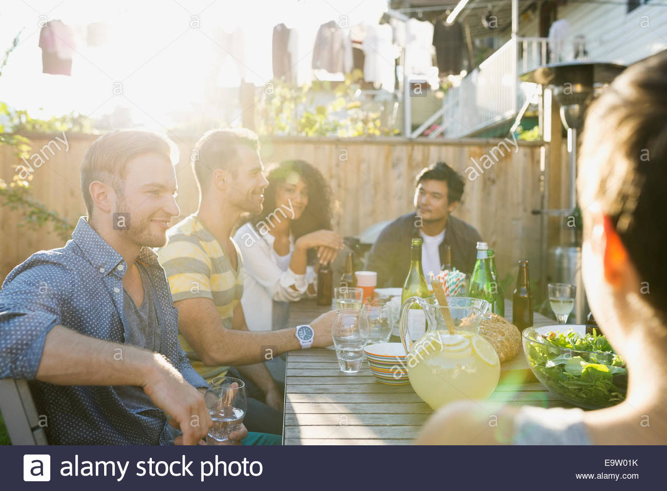 friends eating and drinking at backyard barbecue stock photo