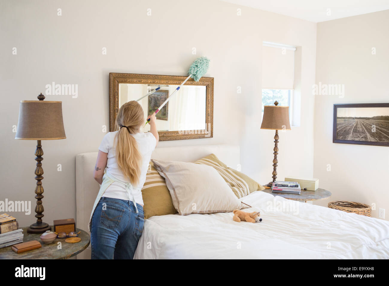 Young Woman Cleaning Bedroom With Green Cleaning Products