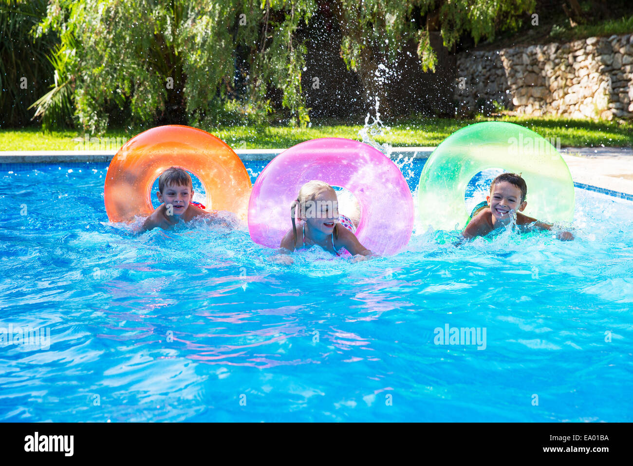 Three children racing on inflatable rings in garden for Kids swimming pool garden
