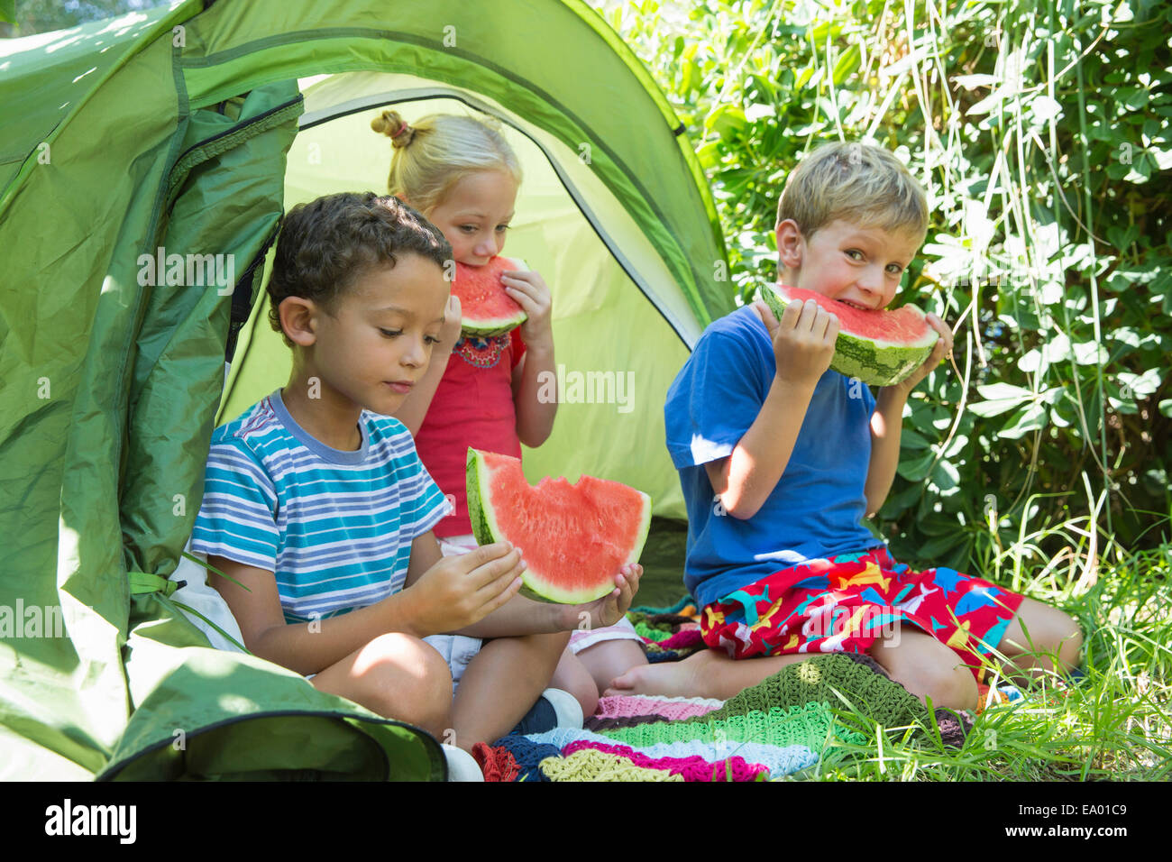 Three children eating watermelon slices in garden tent  sc 1 st  Alamy & Three children eating watermelon slices in garden tent Stock Photo ...