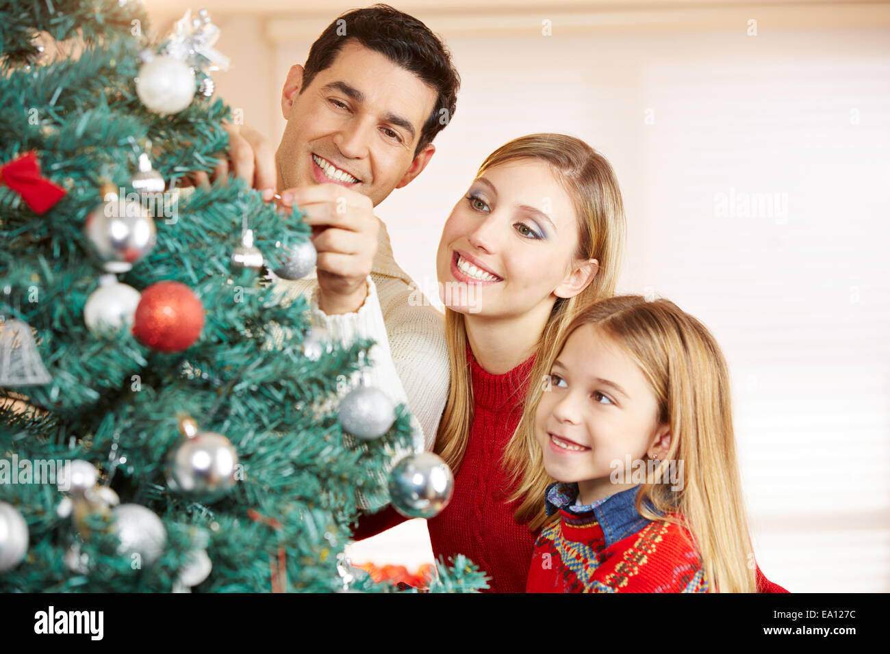 People Decorating For Christmas happy family decorating christmas tree together at home stock