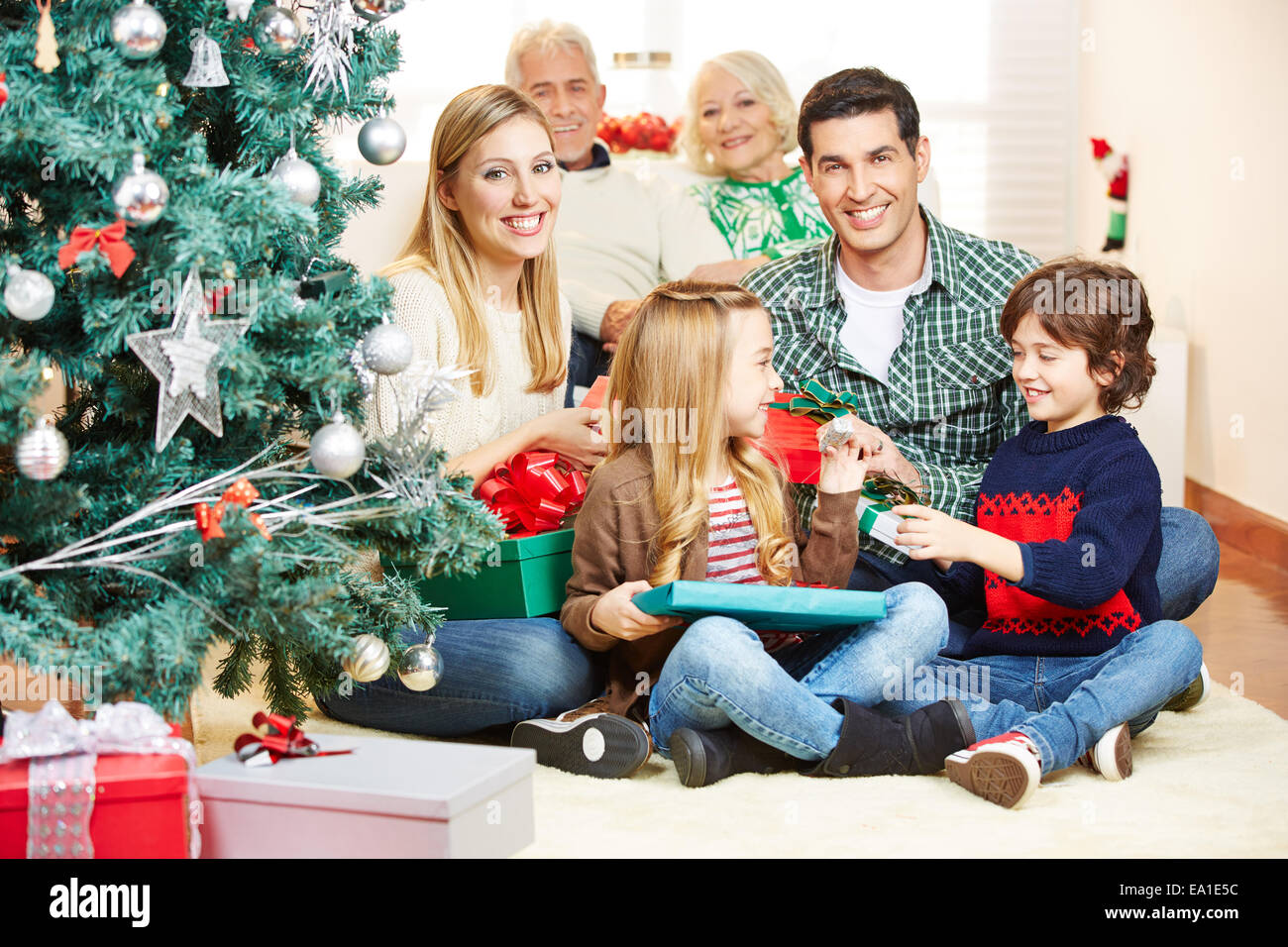 Happy family with grandparents making gift giving at christmas eve happy family with grandparents making gift giving at christmas eve negle Images