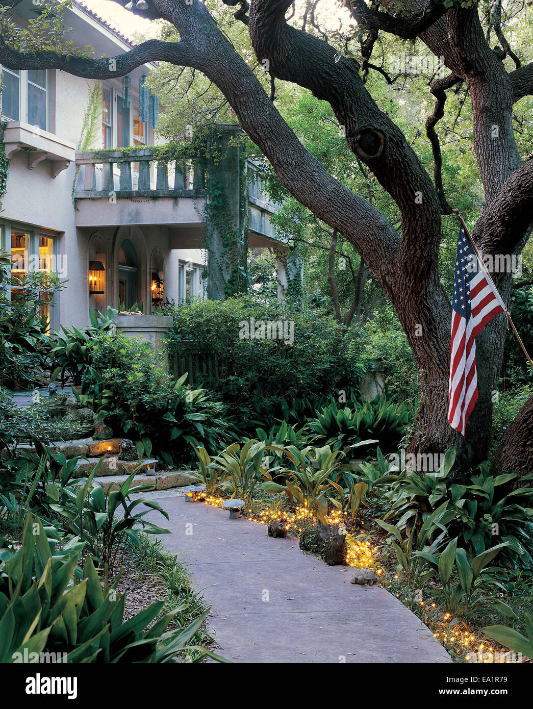 Lit Garden Path With American Flag Leads To Front Door Of Stone